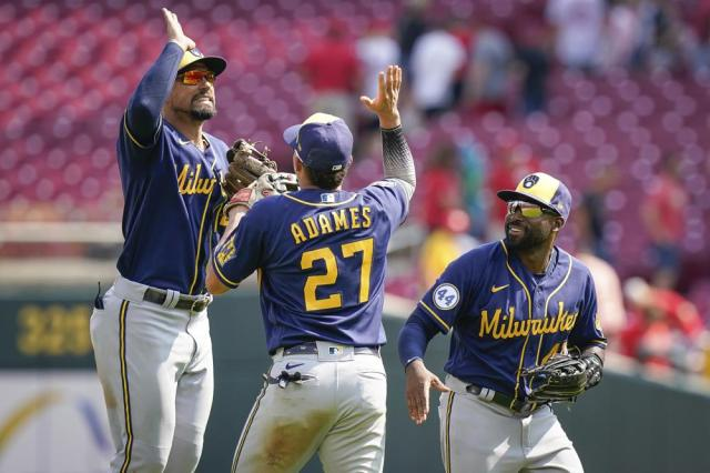 Milwaukee Brewers' Jace Peterson (14) celebrates with Willy Adames (27) after the team's win over the Cincinnati Reds in a baseball game in Cincinnati, Sunday, July 18, 2021. (AP Photo/Bryan Woolston)