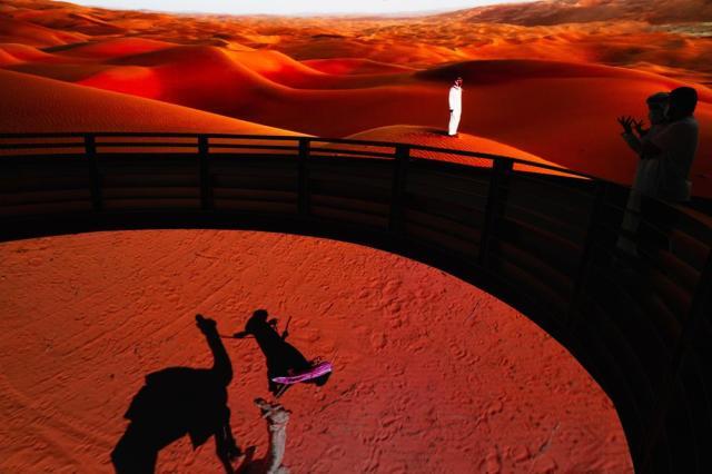 Men watch a display at the Saudi Arabia pavilion at Expo 2020 in Dubai, United Arab Emirates, Saturday, Oct. 2, 2021. (AP Photo/Jon Gambrell)