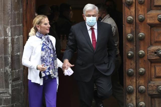 Mexican President Andres Manuel Lopez Obrador, right, wearing protective face masks to help curb the spread of the coronavirus, and first lady Beatriz Gutierrez walk away after voting in Mexico City, Sunday, June 6, 2021. Mexicans on Sunday were electing the entire lower house of Congress, almost half the country's governors and most mayors in a vote that will determine if Obrador's Morena party gets a legislative majority. (AP Photo/Marco Ugarte)