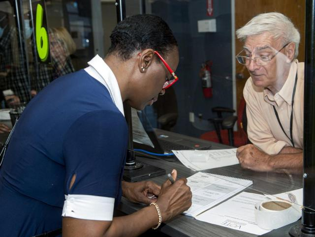 In this July 7, 2021, photo Nina Turner, a candidate running in a special Democratic primary election for Ohio's 11th Congressional District signs in as election official Fred Smith looks on at the Cuyahoga County Board of Elections before casting her vote in Cleveland. (AP Photo/Phil Long)