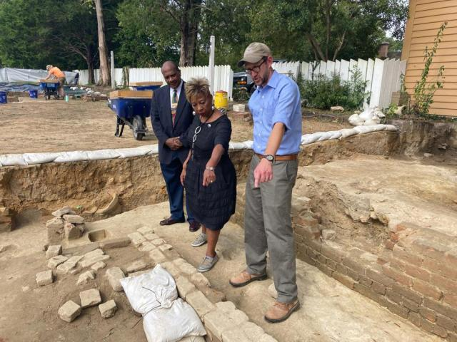 Reginald F. Davis, from left, pastor of First Baptist Church in Williamsburg, Connie Matthews Harshaw, a member of First Baptist, and Jack Gary, Colonial Williamsburg's director of archaeology, stand at the brick-and-mortar foundation of one the oldest Black churches in the U.S. on Wednesday, Oct. 6, 2021, in Williamsburg, Va. Colonial Williamsburg announced Thursday Oct. 7, that the foundation had been unearthed by archeologists. (AP Photo/Ben Finley)