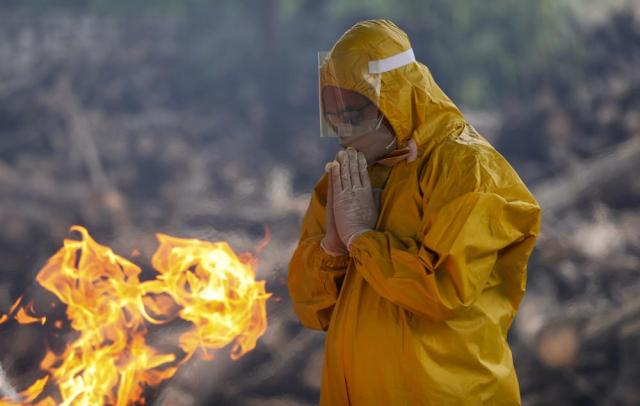 A family member prays as he performs the last rites of a person who died due to COVID-19 at a crematorium in Jammu, India, Monday, May 31, 2021. (AP Photo/Channi Anand)