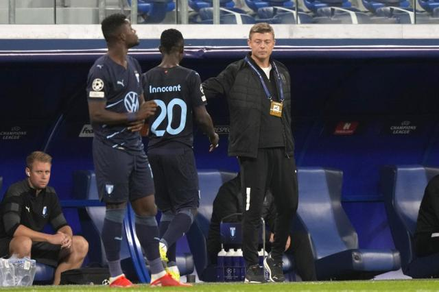 Malmo's head coach Jon Dahl Tomasson shakes hands with Malmo's Bonke Innocent during the Champions League, group H, soccer match, between Zenit St. Petersburg and Malmo at the Gazprom Arena in St.Petersburg, Russia, Wednesday, Sept. 29, 2021. (AP Photo/Dmitry Lovetsky)