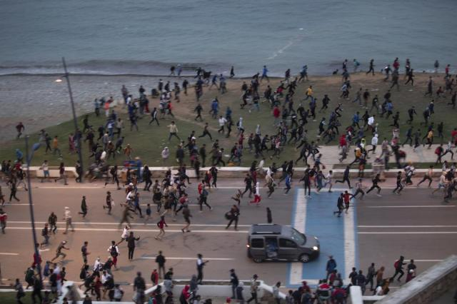 FILE - In this May 19, 2021, file photo, Moroccan youth run for cover as they clash with Moroccan security forces while trying to cross to the Spanish enclave of Ceuta from Fnideq, Morocco. Thousands of would-be migrants converged on Fnideq this week, part of an extraordinary mass effort to swim or scale barbed-wire fences to get into Spain for a chance at a new life. (AP Photo/Mosa'ab Elshamy, File)