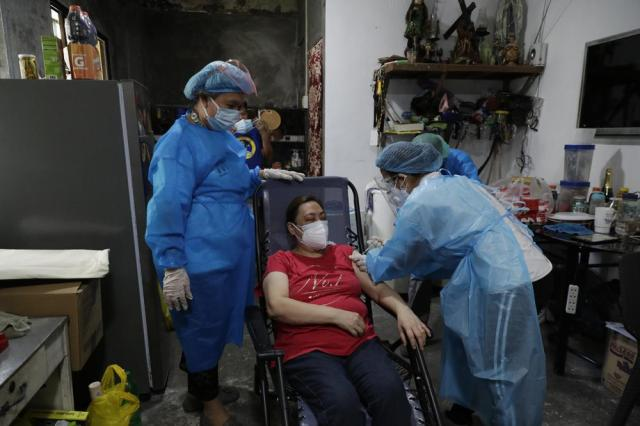 A health worker inoculates a resident with China's Sinovac COVID-19 vaccine inside her home in Manila, Philippines on Wednesday, May 19, 2021. Philippine President Rodrigo Duterte has eased a lockdown in the bustling capital and adjacent provinces to fight economic recession and hunger but has still barred public gatherings this month, when many Roman Catholic festivals are held. (AP Photo/Aaron Favila)