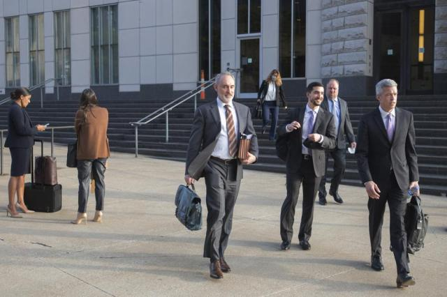 Attorneys and staff associated with a federal trial of pharmacies, CVS, Walgreens, Giant Eagle and Walmart leave the Carl B. Stokes Federal Courthouse in Cleveland, Monday, Oct. 4, 2021. The pharmacies are being sued by Ohio counties Lake and Trumbull for their part in the opioid crisis. (AP Photo/Phil Long)