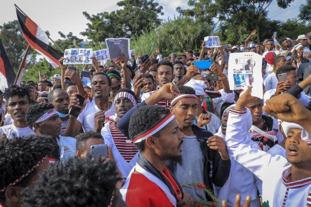 Oromos protest against the government and call for the release of prominent opposition figure Jawar Mohammed and others, seen on placards, during the annual Irreecha festival in the capital Addis Ababa, Ethiopia, Saturday, Oct. 2, 2021. Ethiopia's largest ethnic group, the Oromo, on Saturday celebrated the annual Thanksgiving festival of Irreecha, marking the end of winter where people thank God for the blessings of the past year and wish prosperity for the coming year. (AP Photo)