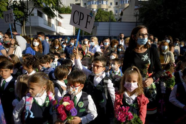 Children wearing face masks react during festivities marking the beginning of the school year at a school in Bucharest, Romania, Monday, Sept. 13, 2021. Children returned to classrooms in Romania, a country with one of the lowest COVID-19 vaccination rates in the European Union, as the daily infection numbers continue to rise.  (AP Photo/Andreea Alexandru)
