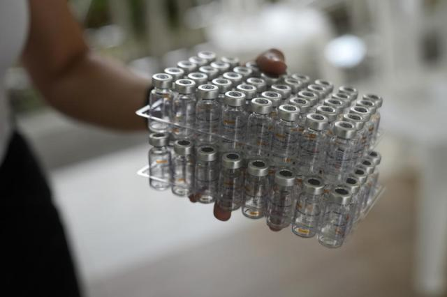 A health worker carries used bottles of China's Sinovac COVID-19 vaccine in Quezon city, Philippines on Monday, Sept. 13, 2021. The government continues to urge Filipinos to get vaccinated as COVID-19 cases keep rising in the country. (AP Photo/Aaron Favila)