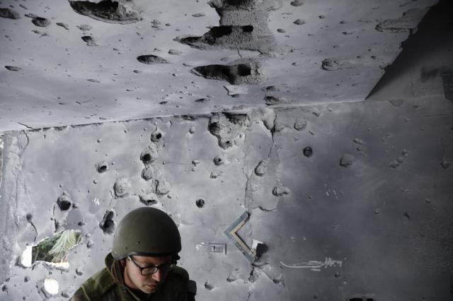 An Israeli soldier inspects the damaged house after it was hit by a rocket fired from the Gaza Strip, In Ashkelon, Israel, Thursday, May 20, 2021. (AP Photo/Ariel Schalit)