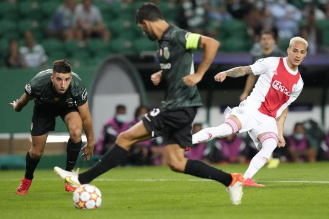 Ajax's Antony, right, passes the ball to Ajax's Sebastien Haller to score his side's opening goal during a Champions League, Group C soccer match between Sporting CP and Ajax at the Alvalade stadium in Lisbon, Wednesday, Sept. 15, 2021. (AP Photo/Armando Franca)