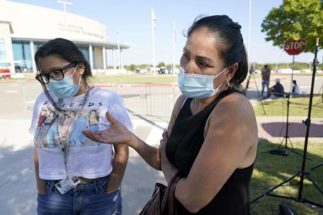 Laura Alabodi, right, responds to questions after picking up her sophomore daughter, left, who did not wish to be identified, from the Mansfield ISD Center For The Performing Arts where they were reunited, Wednesday, Oct. 6, 2021 in Mansfield, Texas. Police in Texas have arrested a student suspected of opening fire during a fight at his Dallas-area high school, leaving four people injured. (AP Photo/Tony Gutierrez)