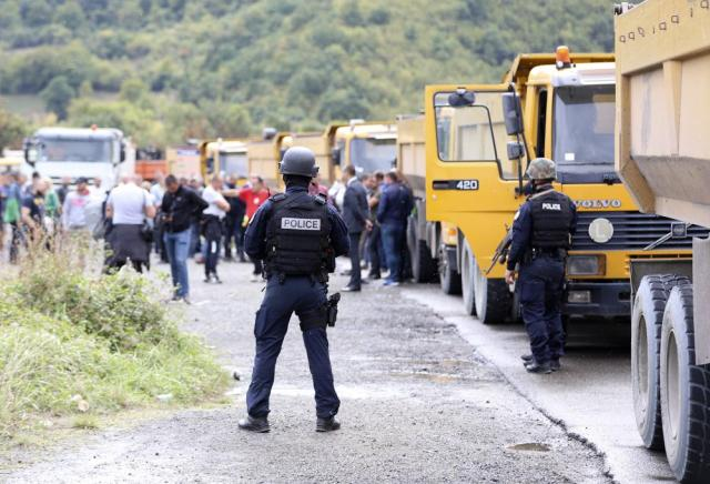 Kosovo special police stand on the road near the northern Kosovo border crossing of Jarinje, Monday, Sept. 20, 2021. Tensions soared Monday at the border between Kosovo and Serbia as Kosovo deployed additional police to implement a rule to remove Serbian license plates from cars entering Kosovo, while Serbs protested the move. (AP Photo/Bojan Slavkovic)