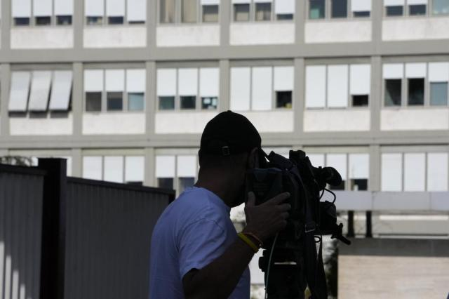 A cameraman films the exterior of Rome's Gemelli Polyclinic where Pope Francis has been hospitalized for a for scheduled surgery for a stenosis, or restriction, of the large intestine, the Vatican said, Sunday, July 4, 2021. The news came just three hours after Francis had cheerfully greeted the public in St. Peter's Square and told them he will go to Hungary and Slovakia in September.  (AP Photo/Alessandra Tarantino)