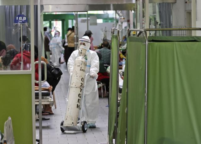 A paramedic pushes an oxygen tank at the emergency ward of an overcrowded hospital amid COVID-19 cases, in Surabaya, East Java, Indonesia, Friday, July 9, 2021. The world's fourth most populous country is running out of oxygen as it endures a devastating wave of coronavirus cases and the government is seeking emergency supplies from other countries, including Singapore and China. (AP Photo/Trisnadi)