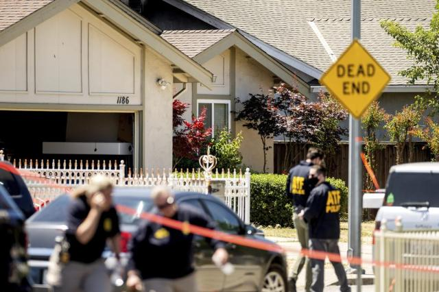 FBI agents approach a home, rear, being investigated in connection to a shooting at a Santa Clara Valley Transportation Authority (VTA) facility on Wednesday, May 26, 2021, in San Jose, Calif. A Santa Clara County sheriff's spokesman said a shooting at the rail yard left at least eight people, including the gunman, dead. (AP Photo/Noah Berger)