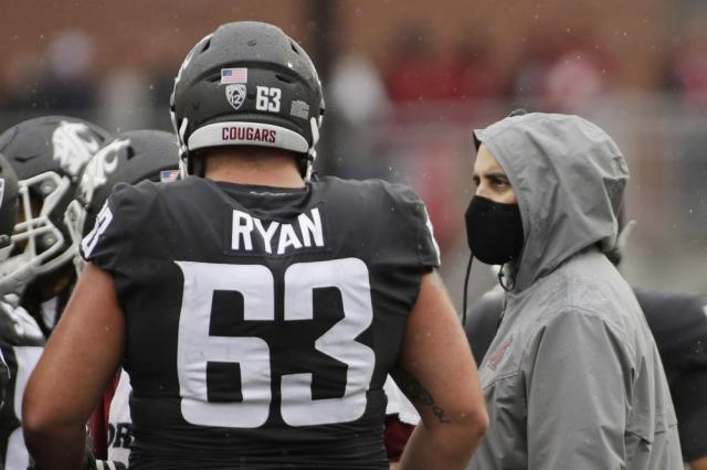 Washington State head coach Nick Rolovich, right, speaks with offensive lineman Liam Ryan during a break in play in the first half of an NCAA college football game against Southern California, Saturday, Sept. 18, 2021, in Pullman, Wash. (AP Photo/Young Kwak)