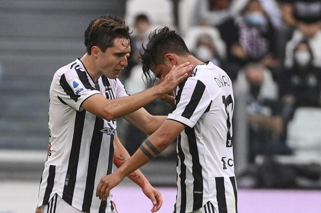 Juventus' Paulo Dybala, right, is consoled by teammate Federico Chiesa as he leaves the pitch after suffering an injury during the Italian Serie A soccer match between Juventus and Sampdoria, in Turin, Italy, Sunday, Sept. 26, 2021. (Marco Alpozzi/LaPresse via AP)