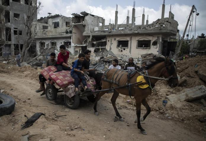 Palestinians on a horse carte loaded with belongings, pass by destroyed homes, to which they returned following a cease-fire reached after an 11-day war between Gaza's Hamas rulers and Israel, in town of Beit Hanoun, northern Gaza Strip, Friday, May 21, 2021. (AP Photo/Khalil Hamra)