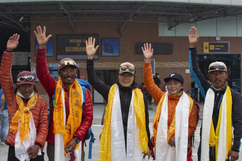 Tsang Yin-hung, 45, center, of Hong Kong who scaled Mount Everest from the base camp in 25 hours and 50 minutes, and became the fastest female climber and her team wave to the media as they arrive in Kathmandu, Nepal, Sunday, May 30, 2021. The Hong Kong teacher and retired attorney from Chicago who became the oldest American to scale Mount Everest, on Sunday returned safely from the mountain where climbing teams have been struggling with bad weather and a coronavirus outbreak. (AP Photo/Bikram Rai)