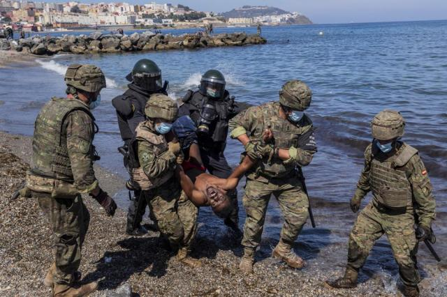 Spanish Army soldiers expel a migrant from the Spanish enclave of Ceuta, on Tuesday, May 18, 2021. (AP Photo/Bernat Armangue)