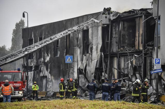 Firefighters work on the site of a plane crash, in San Donato Milanese suburb of Milan, Italy, Sunday, Oct. 3, 2021. According to media reports, a small plane carrying five passengers and the pilot crashed into an apparently vacant office building in a Milan suburb. Their fates were not immediately known. (Claudio Furlan/LaPresse via AP)
