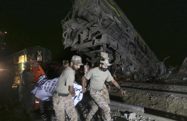 Soldiers and a rescue worker carry the body of a victim after receiving it from the wreckage at the site of a train collision in the Ghotki district, southern Pakistan, late Monday, June 7, 2021. An express train barreled into another that had derailed in Pakistan before dawn Monday, killing dozens of passengers, authorities said. More than 100 were injured, and rescuers and villagers worked throughout the day to search crumpled cars for survivors and the dead. (AP Photo/Fareed Khan)