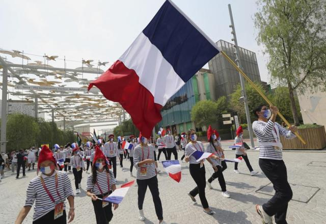 Marchers wave the French and Emirati flags during the French ceremonial day at the Dubai Expo 2020 in Dubai, United Arab Emirates, Saturday, Oct, 2, 2021. (AP Photo/Kamran Jebreili)