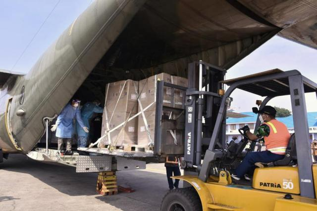In this photo released by Indonesian Armed Forces, a military personnel uses a forklift to unload relief goods from a Singaporean Air Force cargo plane at Halim Perdanakusuma Airbase in Jakarta, Indonesia, Friday, July 9, 2021. The world's fourth most populous country is running out of oxygen as it endures a devastating wave of coronavirus cases and the government is seeking emergency supplies from other countries, including Singapore and China. (Indonesian Armed Forces via AP)