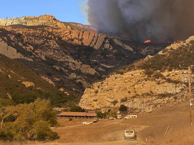 In this photo provided by the Santa Barbara County Fire Department, a wildfire burns Tuesday, Oct. 12, 2021, near a ranch off Highway 101 in Santa Barbara County, Calif. (Mike Eliason/Santa Barbara County Fire via AP)