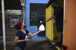 An island already beset with economic woes, Puerto Rico will slowly reopen business under strict guidelines
