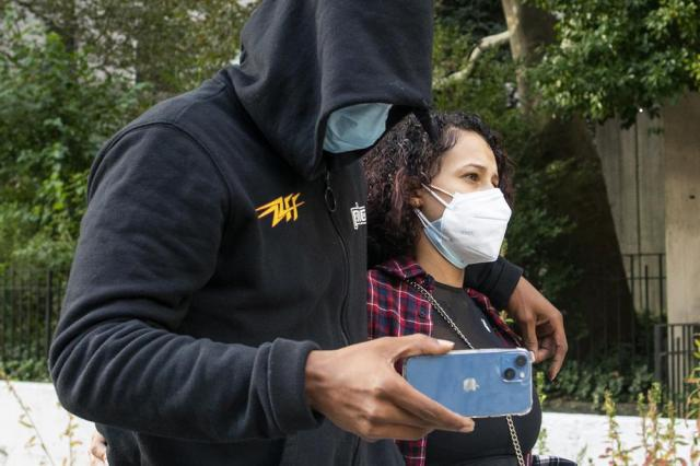 Former NBA basketball player Sebastian Telfair, left, records journalists on his phone as he departs Manhattan Federal Court, Thursday, Oct. 7, 2021, in New York. Federal authorities say 18 former NBA players, including Telfair, have been charged with allegedly pocketing $2.5 million illegally by defrauding the league's health and welfare benefit plan. (AP Photo/Eduardo Munoz Alvarez)