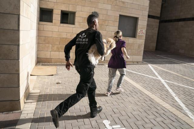 Pedestrians run to a bomb shelter as sirens blare to warn of incoming missiles fire from the Gaza Strip, Thursday, May 20, 2021, in Ashkelon, southern Israel. (AP Photo/John Minchillo)