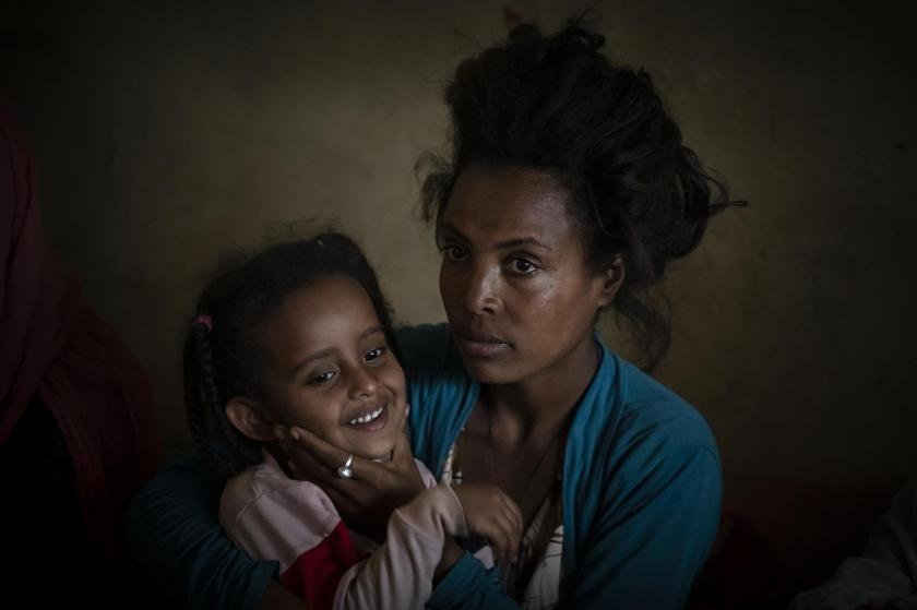 """Smret Kalayu, 25, from Dengelat, Ethiopia, recounts her escape in April while Eritrean forces searched houses and """"watched each other"""" raping women of all ages, as she plays with the daughter of a friend who lives in the same camp for the internally-displaced in Mekele, in the Tigray region of northern Ethiopia Monday, May 10, 2021. Kalayu, who had owned a coffee stall back home, said, """"If there are still Eritreans there, I don't have a plan to go back home. … What can I say? They are worse than beasts. I can't say they are human beings."""" (AP Photo/Ben Curtis)"""
