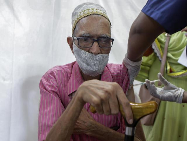 An elderly man gets inoculated against COVID-19 at a vaccination center in Mumbai, India, Monday, May 31, 2020. (AP Photo/Rajanish kakade)