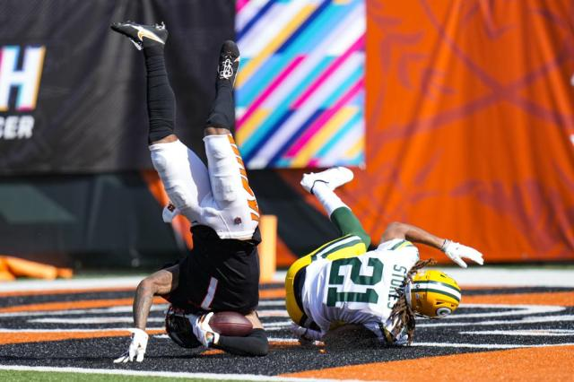 Cincinnati Bengals wide receiver Ja'Marr Chase (1) flips into the end zone for a touchdown as he's hit by Green Bay Packers cornerback Eric Stokes (21) in the second half of an NFL football game in Cincinnati, Sunday, Oct. 10, 2021. (AP Photo/AJ Mast)