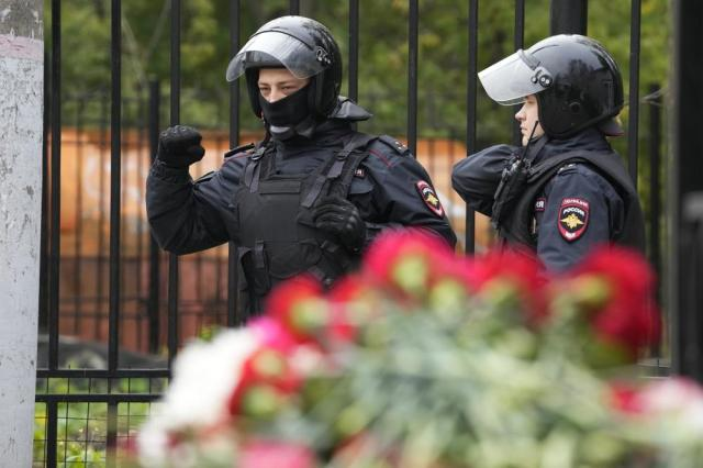 Police officers guard an area outside the  Perm State University following a campus shooting in Perm, about 1,100 kilometers (700 miles) east of Moscow, Russia, Tuesday, Sept. 21, 2021. A student opened fire at the university, leaving a number of people dead and injured, before being shot in a crossfire with police and detained. Beyond saying that he was a student, authorities offered no further information on his identity or a possible motive. (AP Photo/Dmitri Lovetsky)