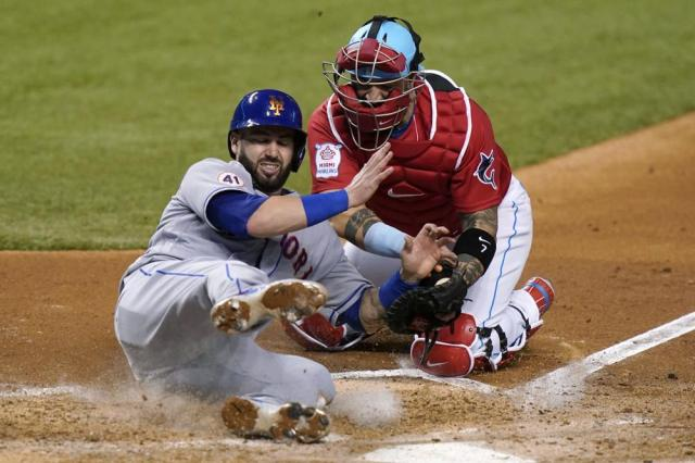 New York Mets' Tomas Nido, left, is tagged out by Miami Marlins catcher Sandy Leon during the fourth inning of a baseball game Friday, May 21, 2021, in Miami. (AP Photo/Lynne Sladky)