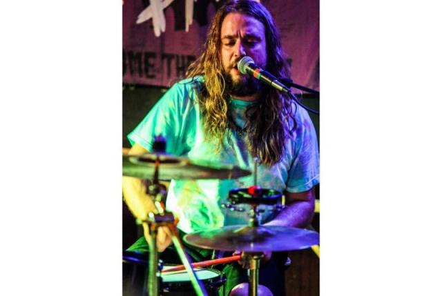 In a photo provided by Russ Boxer, Kevin Clark plays drums as Jess Bess & The Intentions performs at a bar in Highwood, Ill., May 22, 2021. Clark, who played drummer Freddy