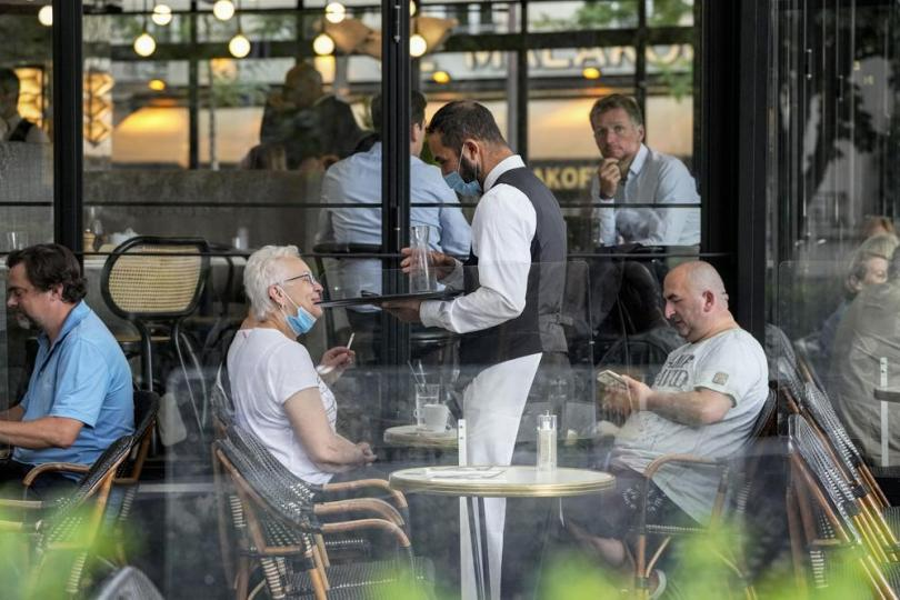 FILE - In this Monday, July 26, 2021 filer, a waiter wearing a face mask to protect against coronavirus serves at a restaurant terrace in Paris. European nations, across the board, have made strides in their vaccination rates in recent months, with or without incentives. No country has made them mandatory, and campaigns to persuade the undecided are a patchwork. (AP Photo/Michel Euler, File)