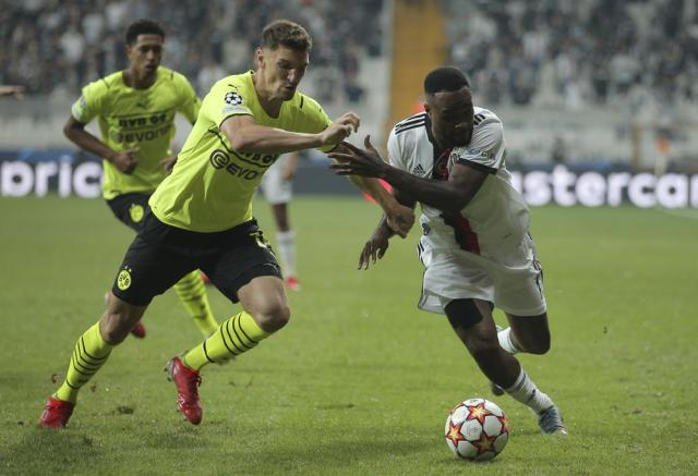 Dortmund's Thomas Meunier, left, challenges for the ball with Besiktas' Cyle Larin during the Champions League Group C soccer match between Besiktas and Borussia Dortmund at the Vodafone Park Stadium in Istanbul, Turkey, Wednesday, Sept. 15, 2021. (AP Photo)