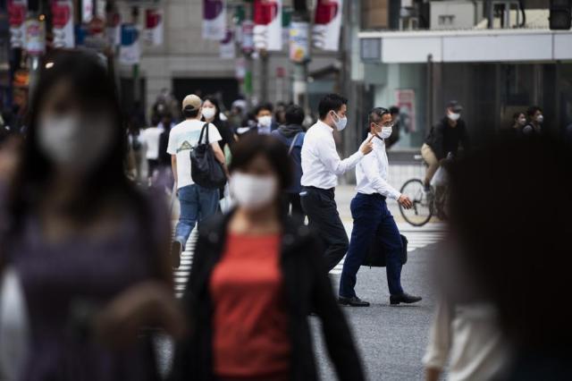 People wearing face masks walk across the famed Shibuya crossing in Tokyo on Thursday, May 20, 2021. (AP Photo/Hiro Komae)