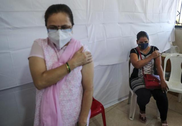 Women hold their arms after receiving Covishield vaccine against the coronavirus at a vaccination center in Mumbai, India, Sunday, July 4, 2021. (AP Photo/Rafiq Maqbool)