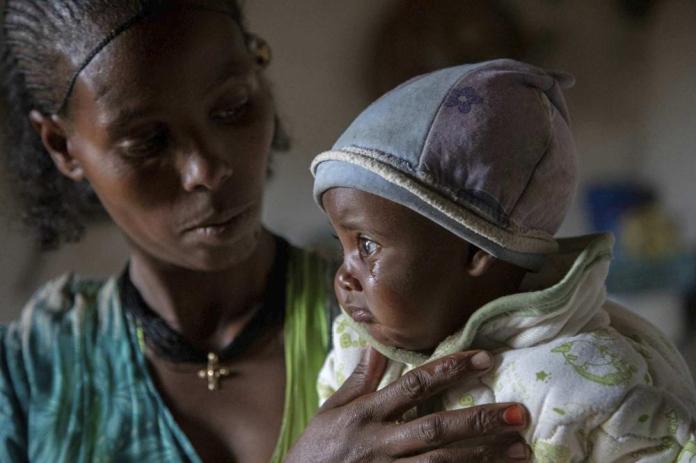 """Mère Ababa, 25 ans, réconforte son bébé Wegahta, 6 mois, qui a été identifié comme gravement souffrant de malnutrition aiguë, à Gijet, dans la région du Tigré, dans le nord de l'Éthiopie, mardi 20 juillet 2021. Pendant des mois, les Nations Unies mettent en garde contre la famine au Tigré et maintenant des documents internes et des témoignages révèlent les premiers décès de faim depuis que le gouvernement éthiopien a imposé en juin ce que l'ONU appelle """"un blocus de facto de l'aide humanitaire"""". (Christine Nesbitt/UNICEF via AP)"""