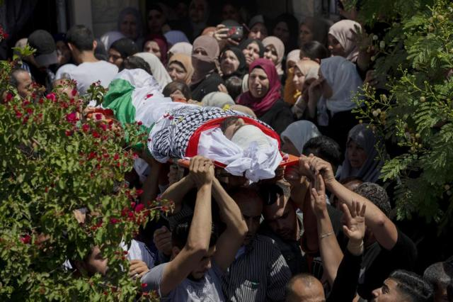 Palestinian mourners carry body of Montaser Jawabreh who was killed in clashes with Israeli forces, during his funeral in Umm Dar village, near the West Bank city of Jenin, Thursday, May 20, 2021. (AP Photo/Majdi Mohammed)