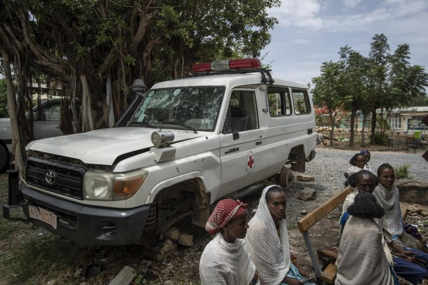 An ambulance said by residents to have been damaged and stripped for parts by Eritrean soldiers sits next to people as they wait to be seen at a medical clinic in Abi Adi, in the Tigray region of northern Ethiopia Tuesday, May 11, 2021. Despite claims by both Ethiopia and Eritrea that they were leaving, Eritrean soldiers are in fact more firmly entrenched than ever in Tigray, The Associated Press has found. (AP Photo/Ben Curtis)