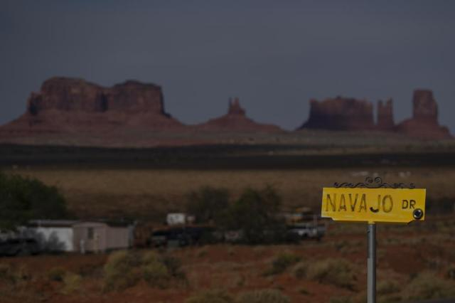 FILE - In this April 30, 2020, file photo, a sign marks Navajo Drive as Sentinel Mesa, homes and other structures in Oljato-Monument Valley, Utah on the Navajo Reservation, stand in the distance. Navajos clamored to enroll or fix their records as the tribe offered hardship assistance payments from last year's federal Coronavirus Aid, Relief and Economic Security Act. That boosted the number the tribe had in its vital statistics from about 310,000 to nearly 400,000 enrolled Navajos. The figure tops the Cherokee Nation's enrollment of 392,000. (AP Photo/Carolyn Kaster, File)