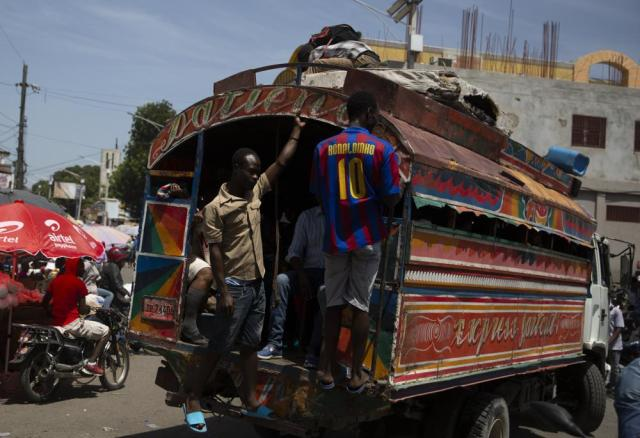People take a ride in a bus at a market in Port-au-Prince, Sunday, July 11, 2021, four days after the assassination of Haitian President Jovenel Moise. (AP Photo/Joseph Odelyn)