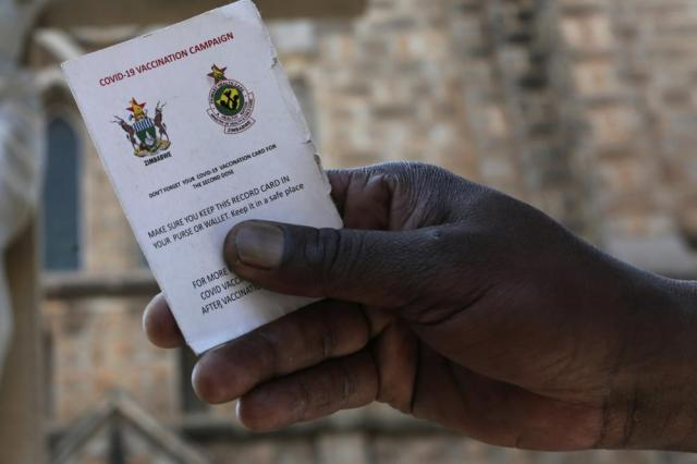 A government worker shows his vaccination card in Harare, Zimbabwe on Sunday, Sept, 19, 2021. Many employers in Zimbabwe are mandating COVID-19 vaccines for their staff, and the government has its own requirement that its 500,000 employees get the shots. (AP Photo/Tsvangirayi Mukwazhi)