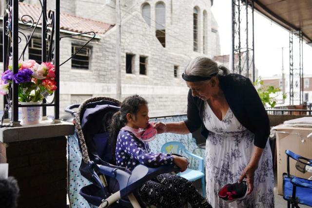 Amanda Brebe, 75, tends to her granddaughter Zuniga Gonzales, 7, in the Kensington section of Philadelphia, Sunday, May 16, 2021. (AP Photo/Matt Rourke)